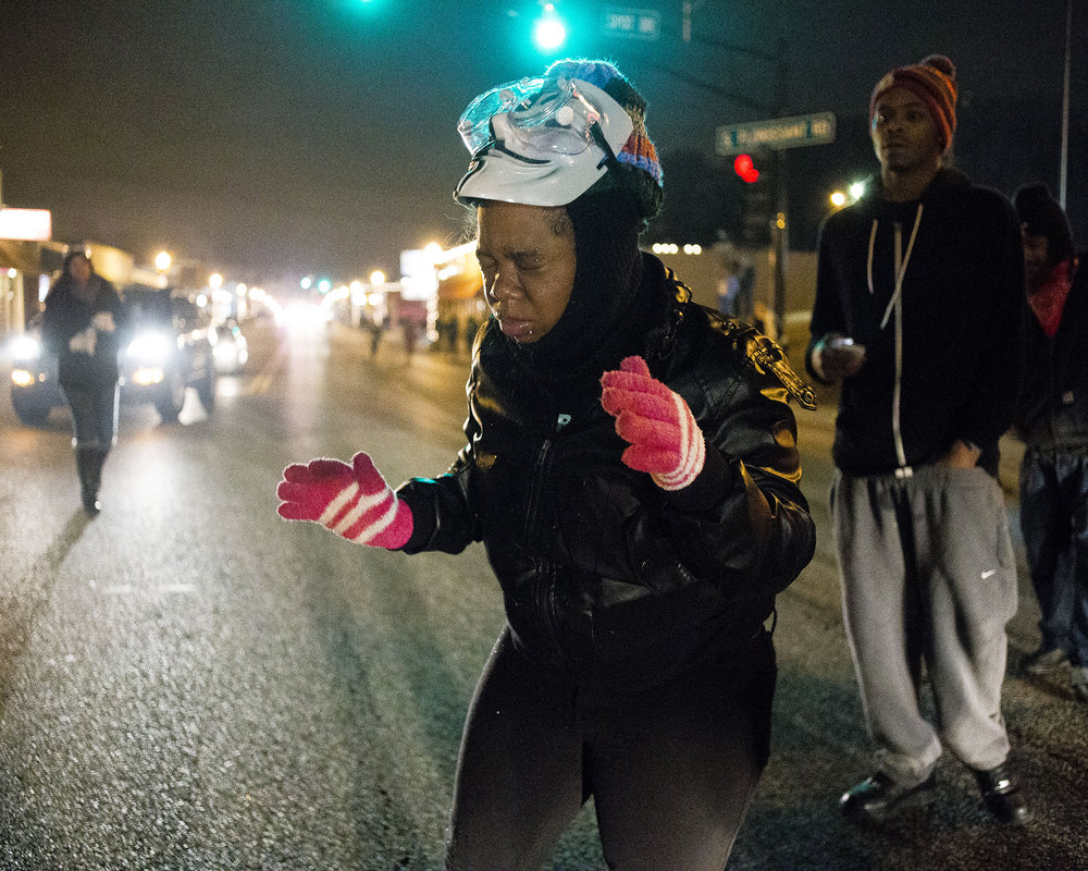 A protester closes her eyes on the street after police sprayed tear gas at her on Nov. 24, 2014, Ferguson, MO.