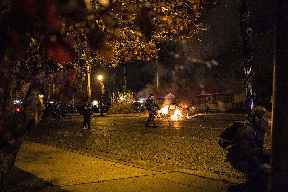 A police vehicle burns while police asks protesters to remain on the sidewalk on Nov. 24, 2014 in Ferguson, MO.