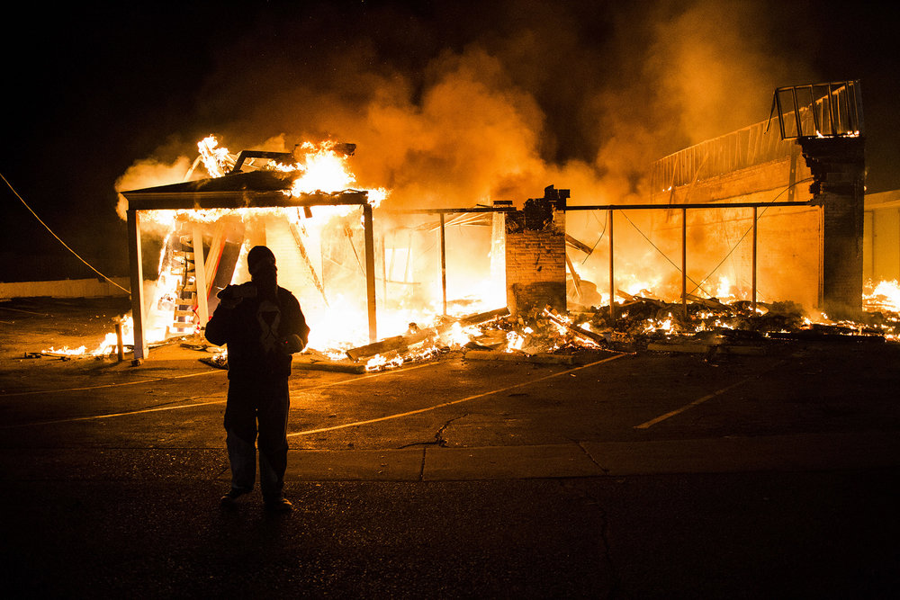 A protester films the scene after protesters set fire to a commercial building on Nov. 24, 2014 in Ferguson, MO.