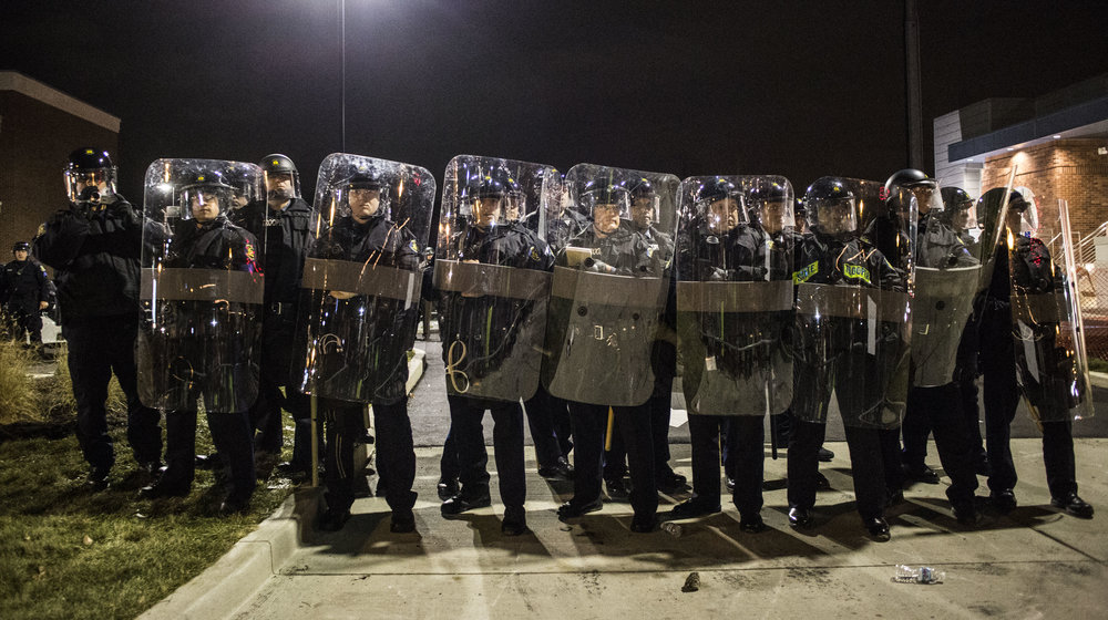 Police guard the Police Department building as protesters throw empty bottles at them on Nov. 24, 2014 in Ferguson, MO.