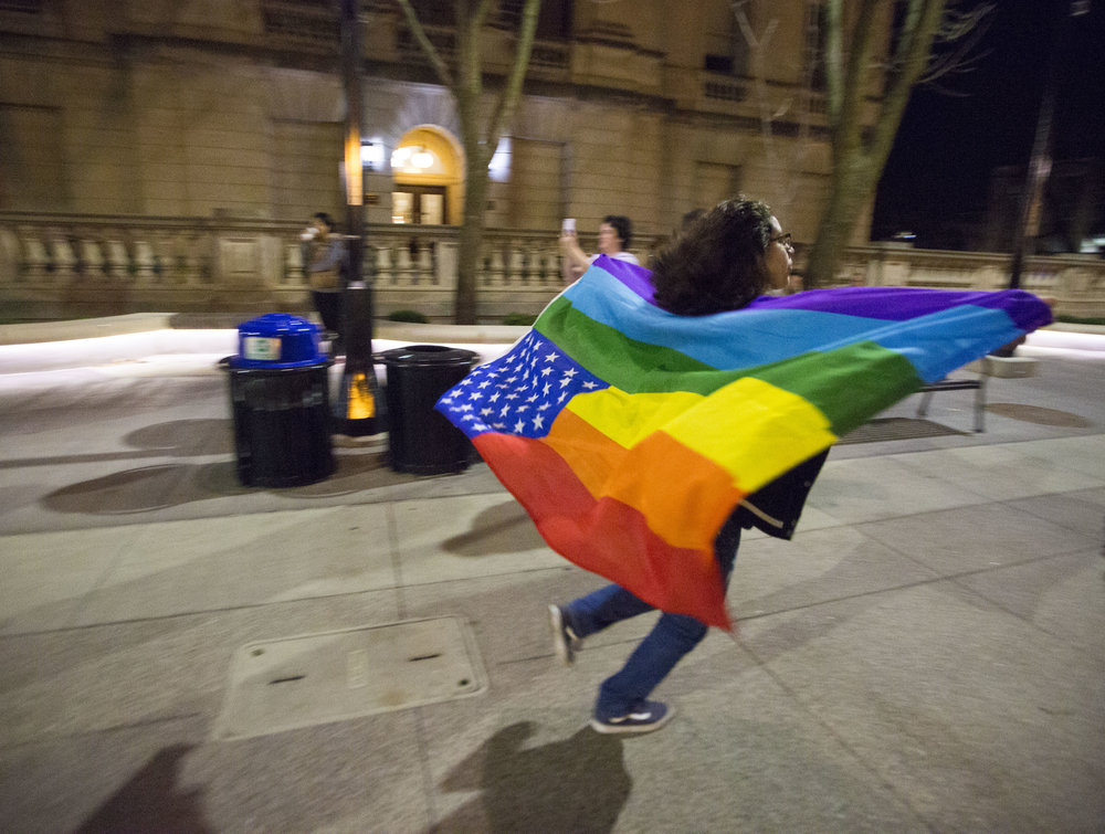 A UW-Madison student wears a rainbow flag and runs down Bascon Hill during an anti-Trump rally on Nov 10, 2016 in Madison, WI.