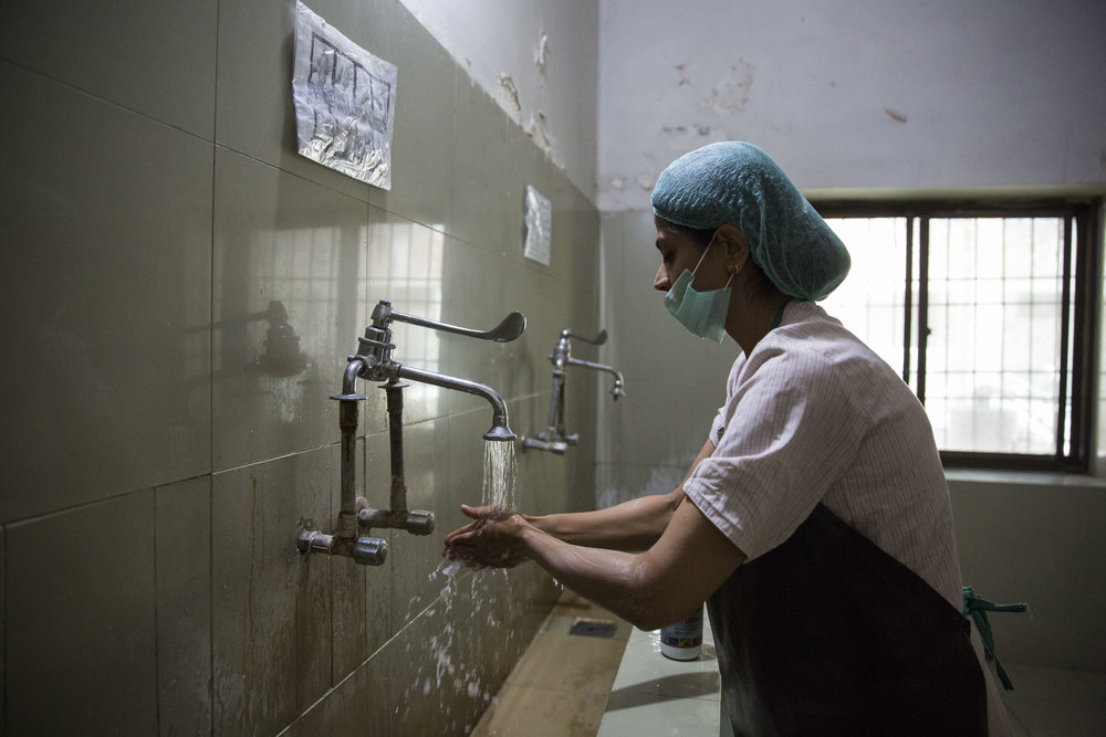 Dr. Sadia Khan washes her hands before entering the operation theatre.