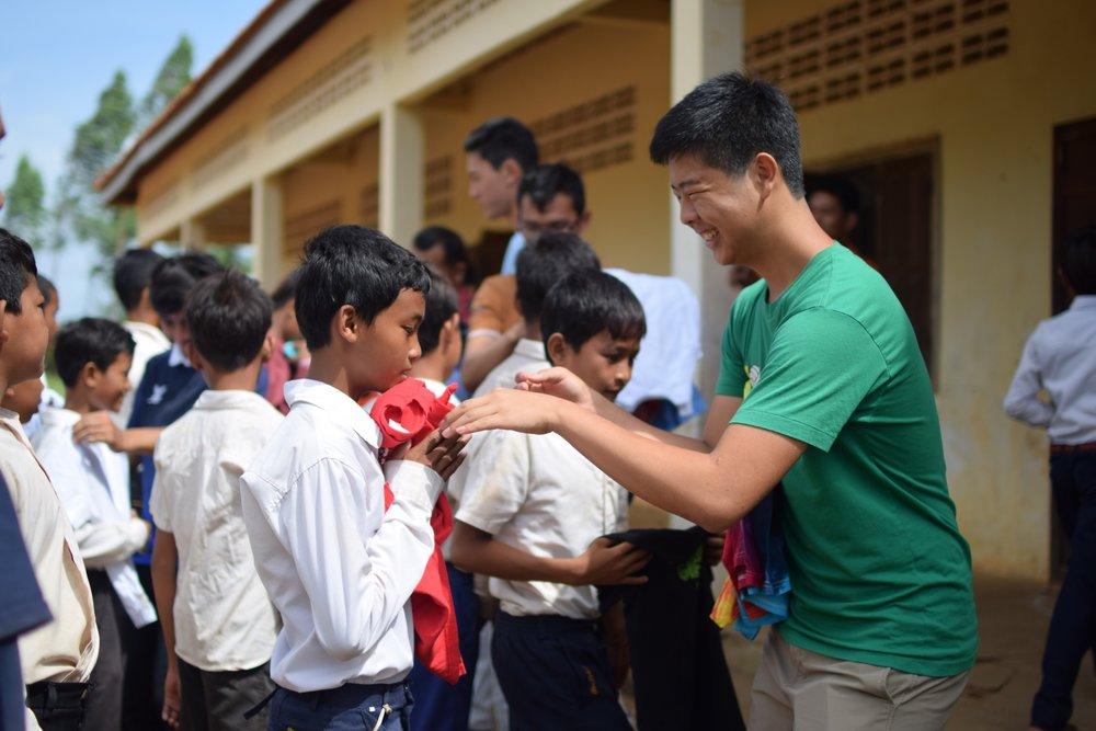 TASSEL volunteer Adam Kim distributing clothing to the students of the Banan TASSEL School, 2016.