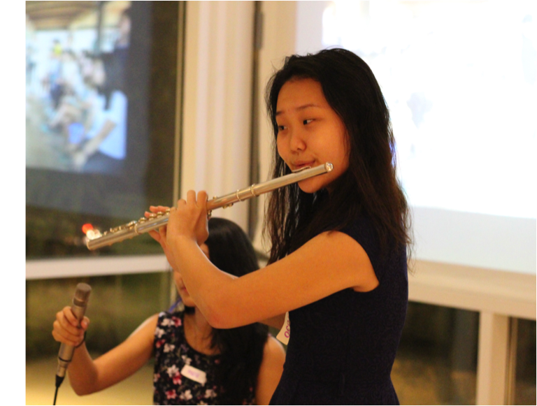 TASSEL volunteer Jeniffer performing on the flute.