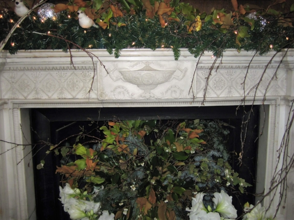 One of the antique marble fireplace surrounds with birds, branches and Christmas gardland.