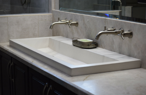 Close up of the sink with wall fixtures, quartzite counter, and back splash and shower tile.
