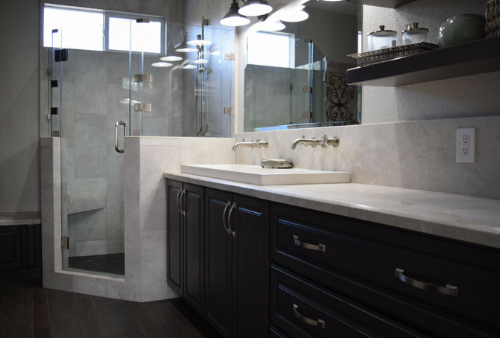 The gray stained cabinetry and top mounted double sink with wall fixtures.