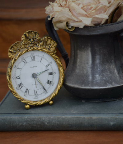 A monogrammed pewter sugar bowl, dried peony, old book and globe alarm clock make a pretty vignette.