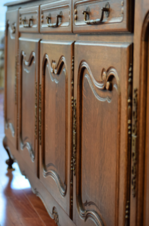 An antique French enfilade adds a sense of history with its tiger oak curved paneled doors and ornate hardware.