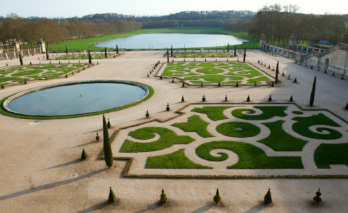 Arabesque parterre gardens symmetrically placed around the the circular water feature.