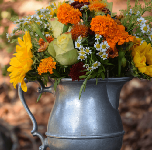 Add a bouquet of fall colored flowers to a pewter pitcher to add a pop of color to your room.