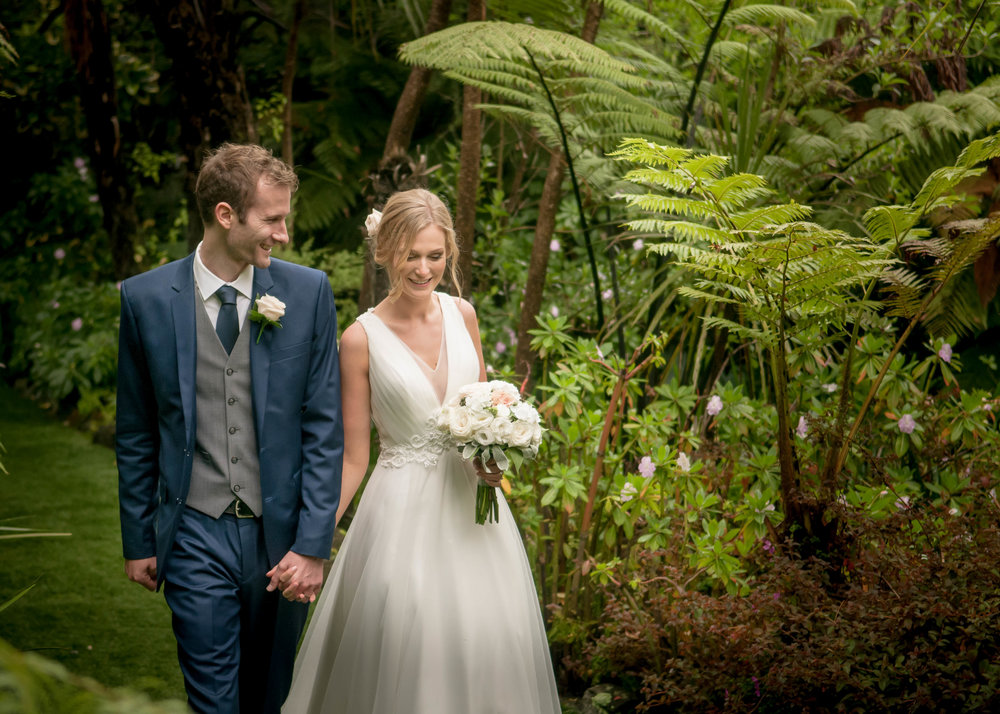 Wedding photo of couple holding hands in a forest