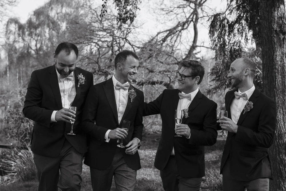 Groom and friends laughing - outdoor wedding photo