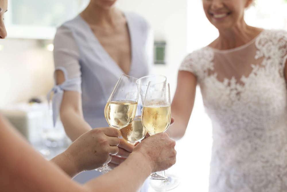 Close of up champagne glasses with bride at wedding ceremony