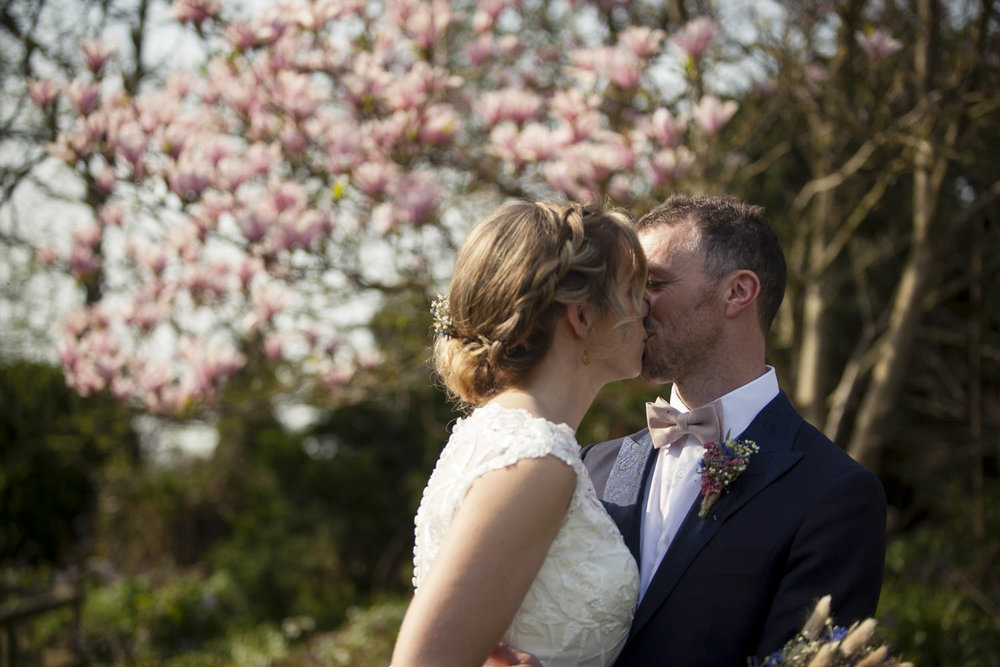Wedding portrait of kissing couple in front of pink blossoms