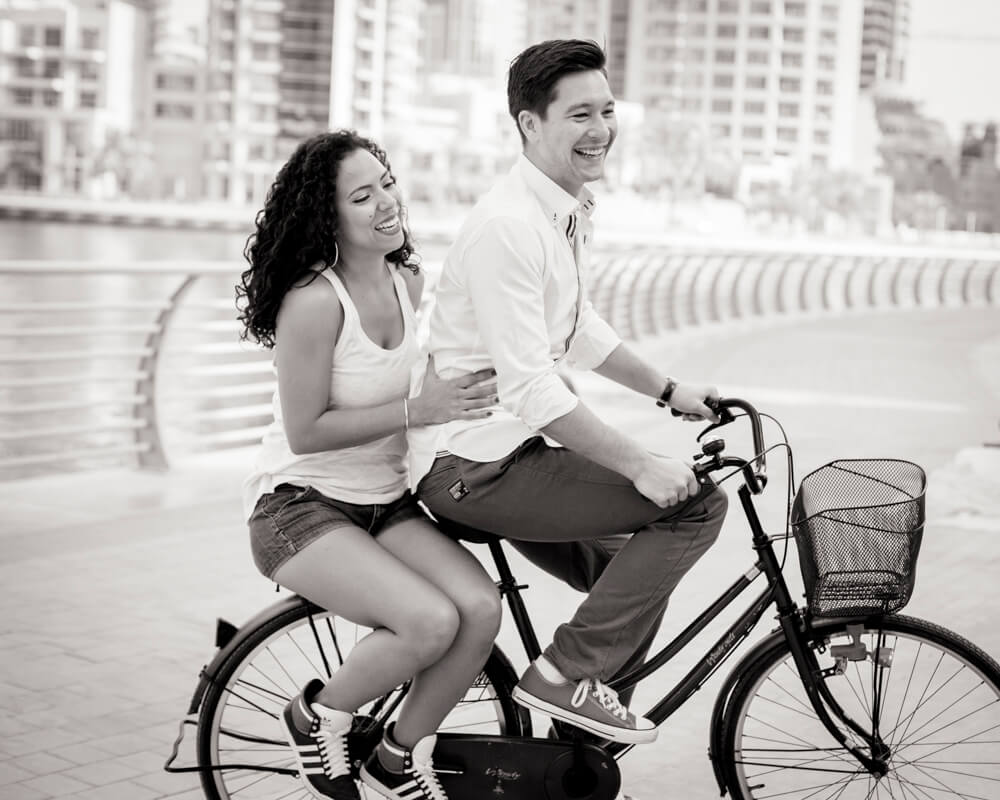 engaged-couple-laughing-on-bike.jpg