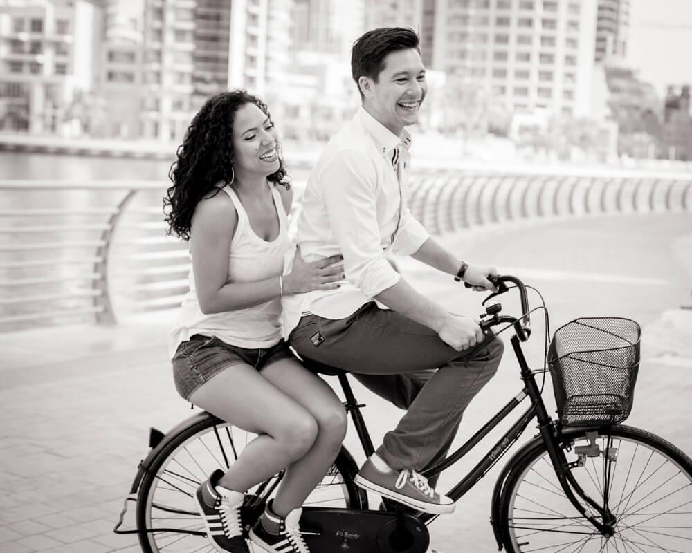 engaged-couple-laughing-on-bike.jpg