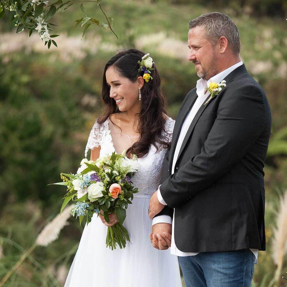 bride-and-groom-with-flower-arch.jpg