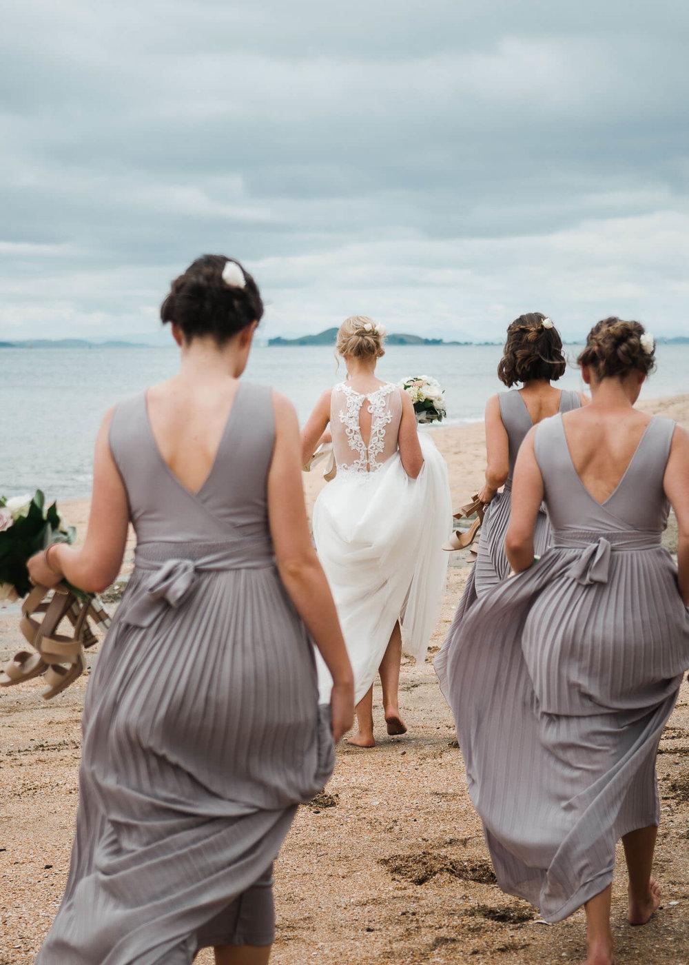 bride-and-bridesmaids-walk-barefoot-down-beach.jpg