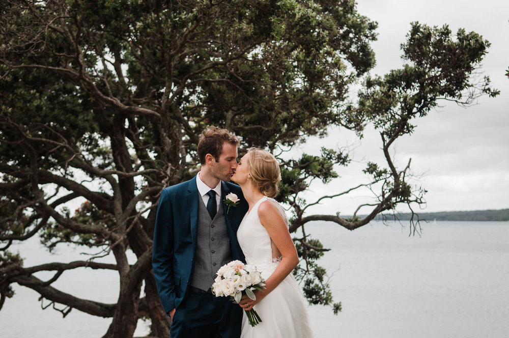 bride-and-groom-kissing-with-tree-in-background.jpg