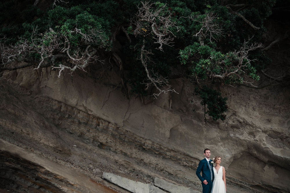 bride-and-groom-stand-with-cliff-in-background.jpg