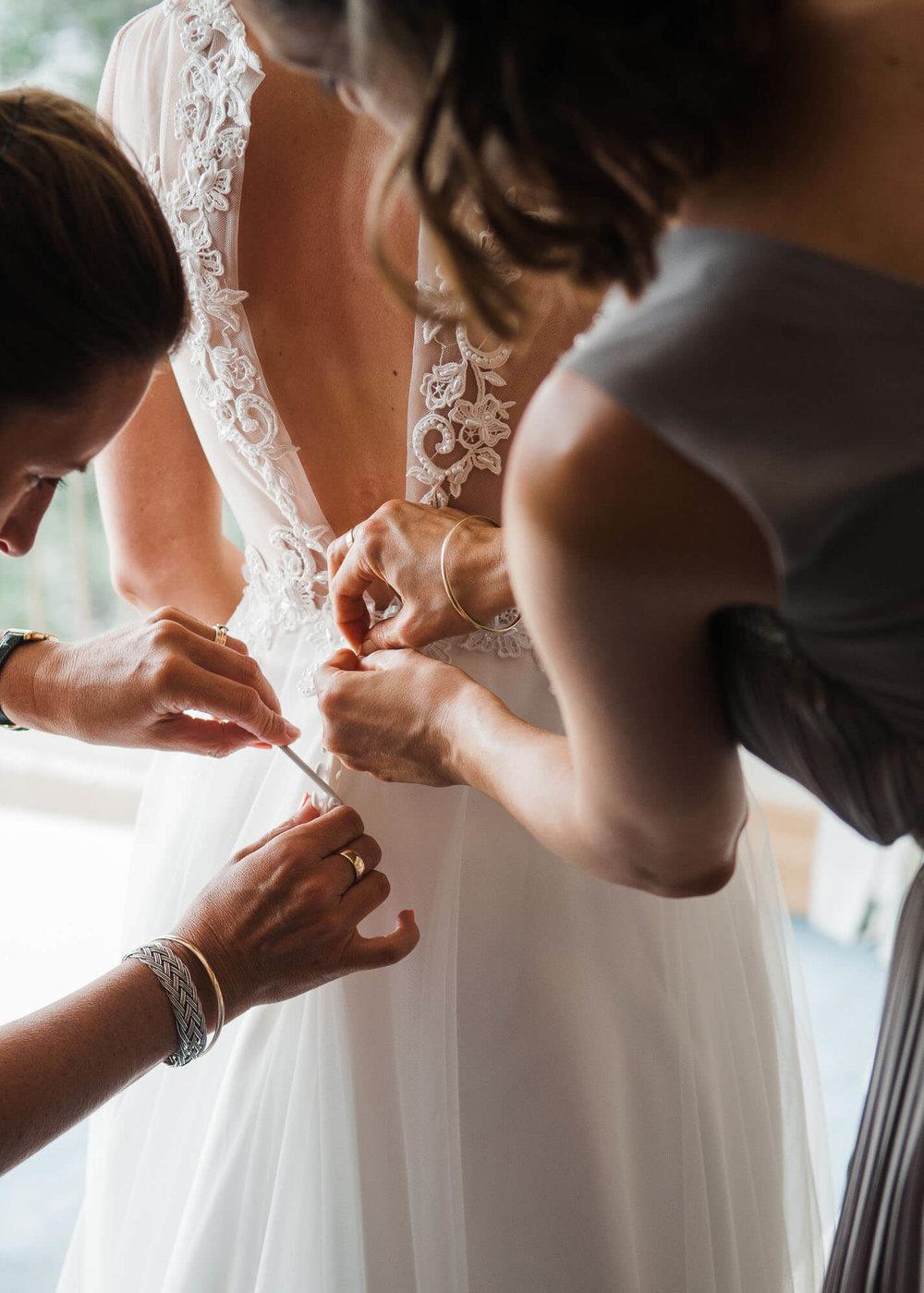 bridesmaids-fasten-brides-dress.jpg