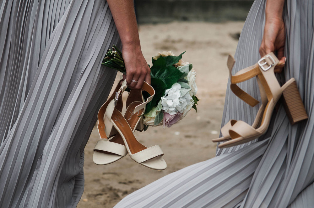 bridesmaids-carry-shoes-on-beach.jpg