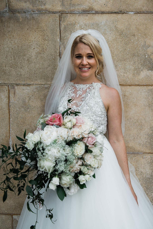 bride-standing-by-brick-wall.jpg