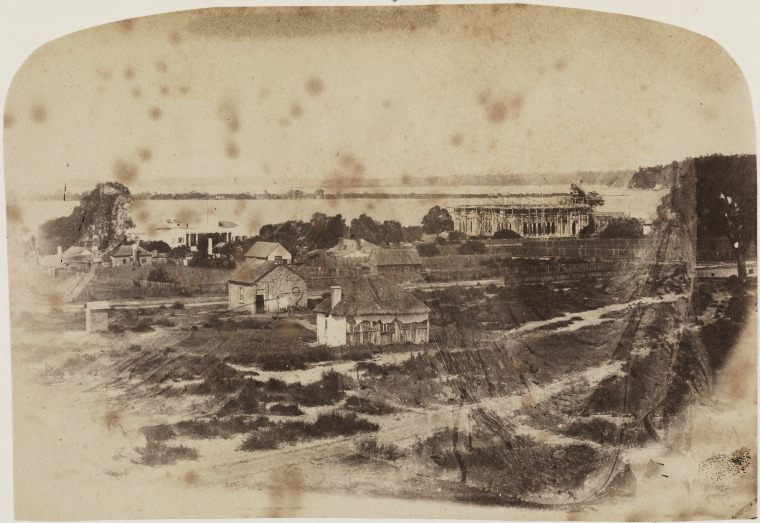 View from Perth Hospital across derelict property to the old Government House and the new Government House under construction, 1861