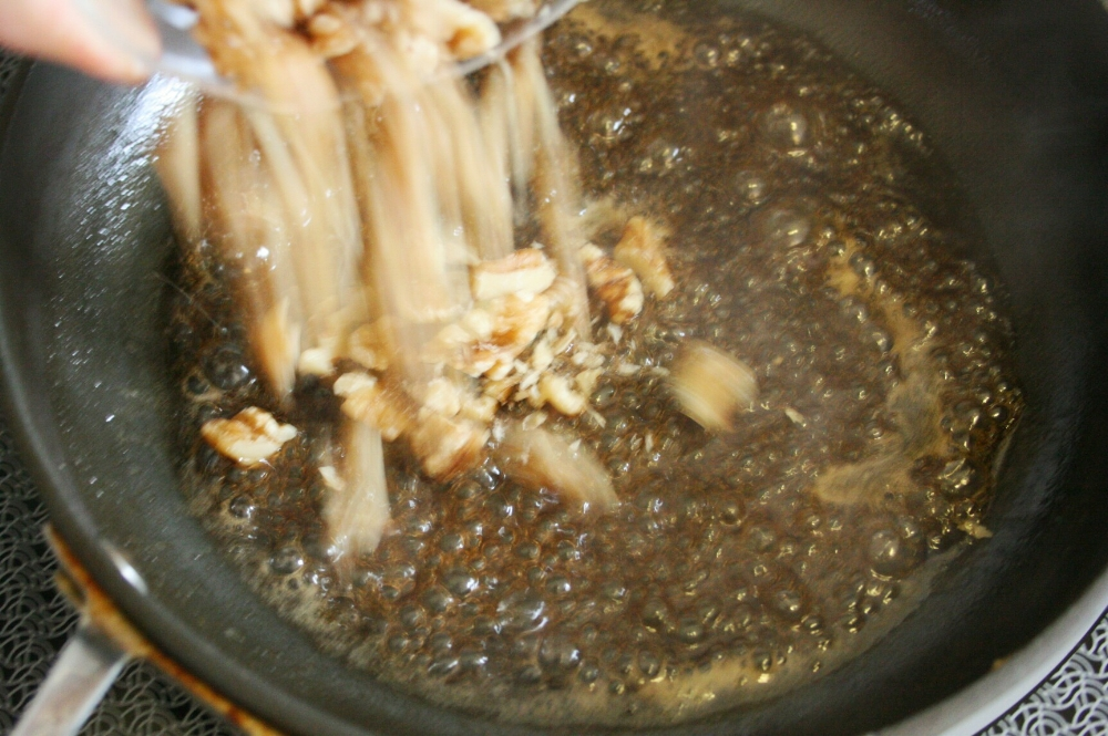 candying waluts in a frying pan with brown sugar and butter