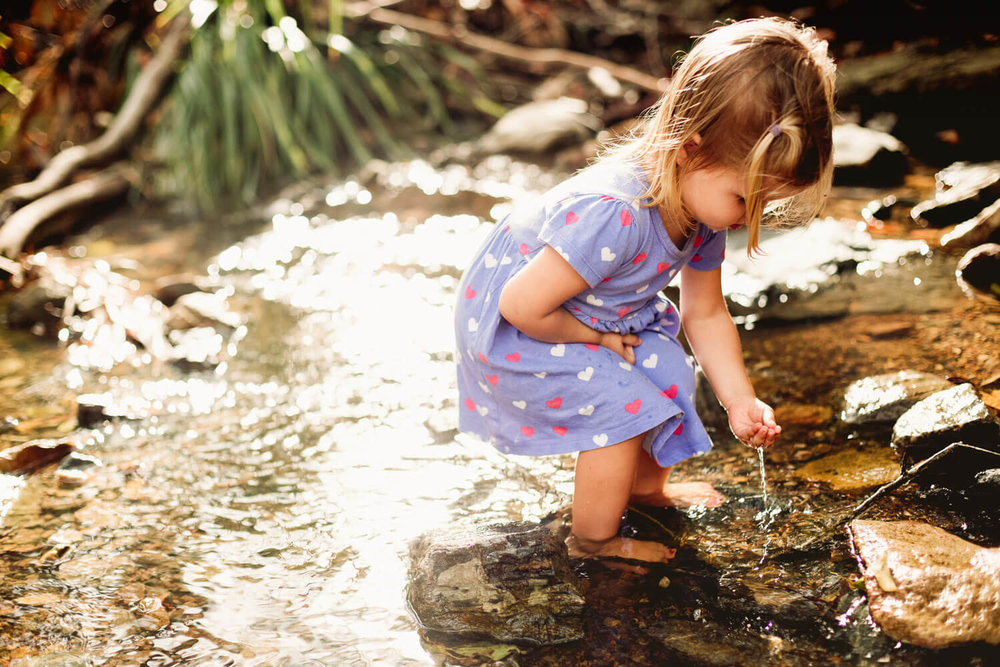 Daughter playing in the creek during family photography shoot at Mt-Coot-tha Brisbane