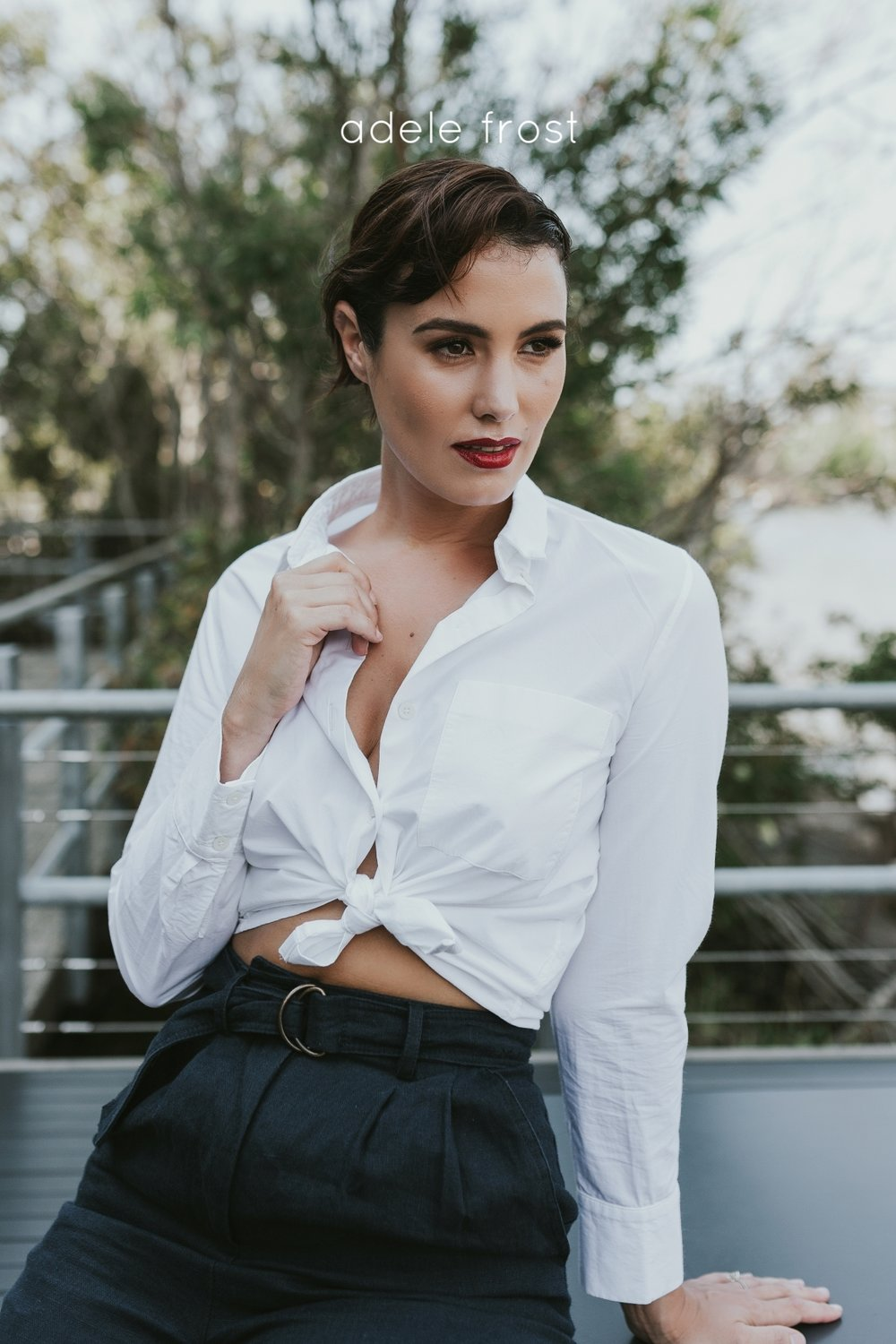 Model poses in crisp white collared shirt and red lipstick.