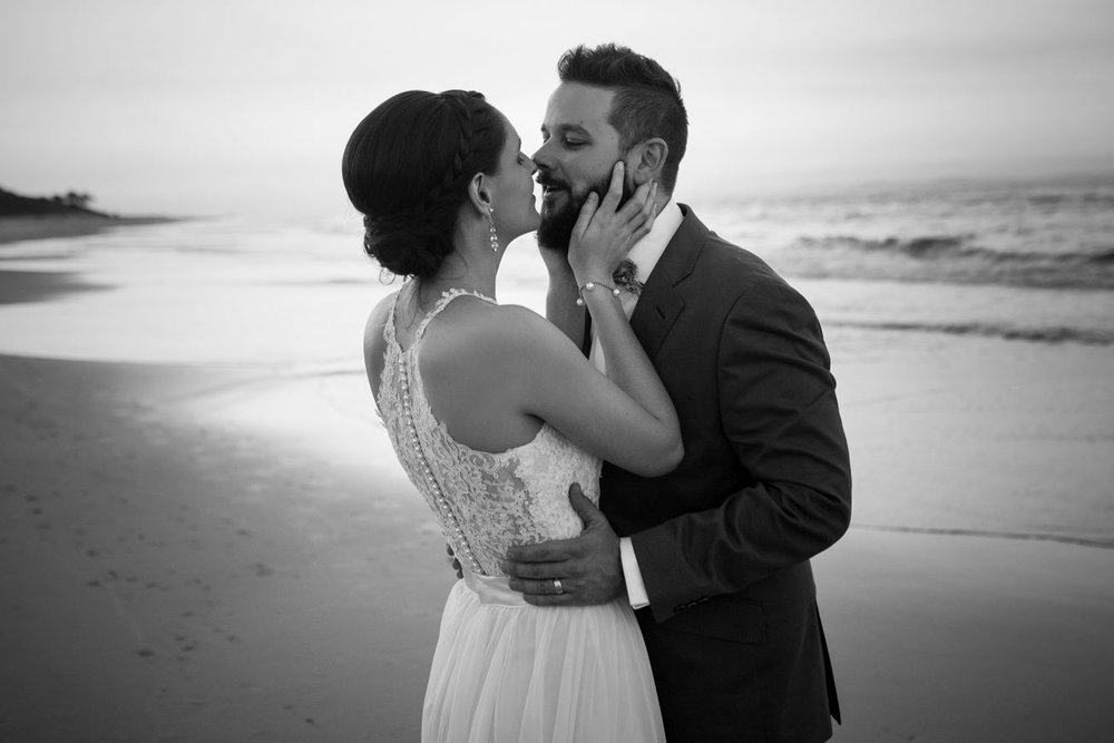 Bride and groom lean in for a kiss at the beach.