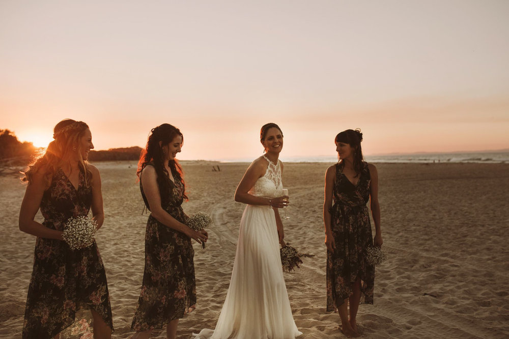 Bride and bridesmaids and a beautiful sunset on the beach at point lookout after an amazing wedding.