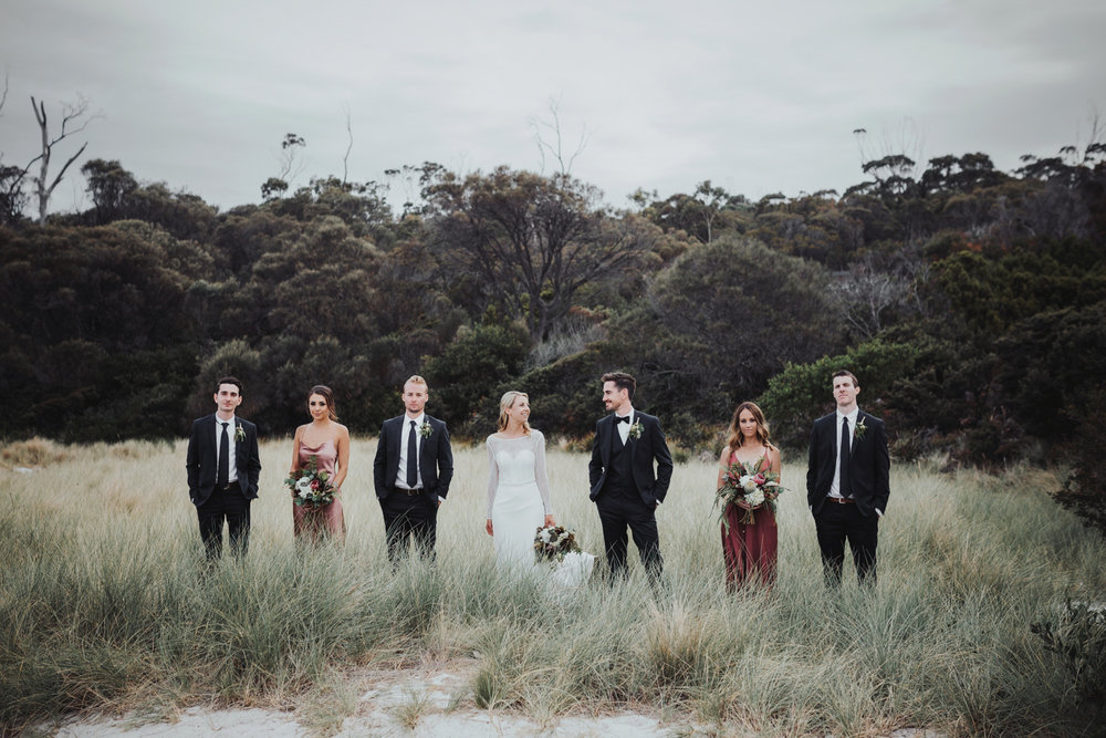 bridal party stands in dunes of bay of fires beach for beautiful portrait.