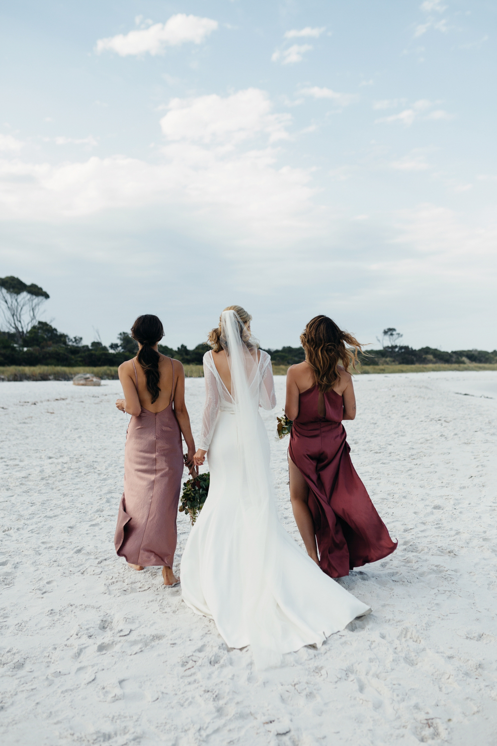 bridesmaids walk with bride on white sandy beach in Tasmania.