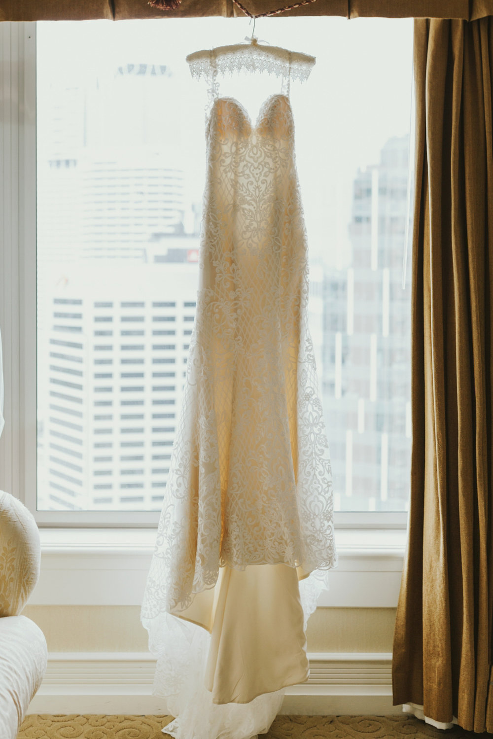 Wedding gown hangs in front of hotel window in Brisbane city.