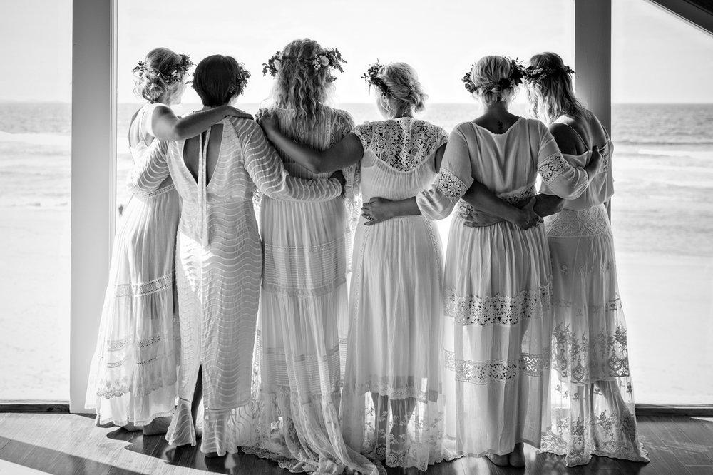 bridesmaids hug wearing lace spell gowns before the wedding in byron bay.