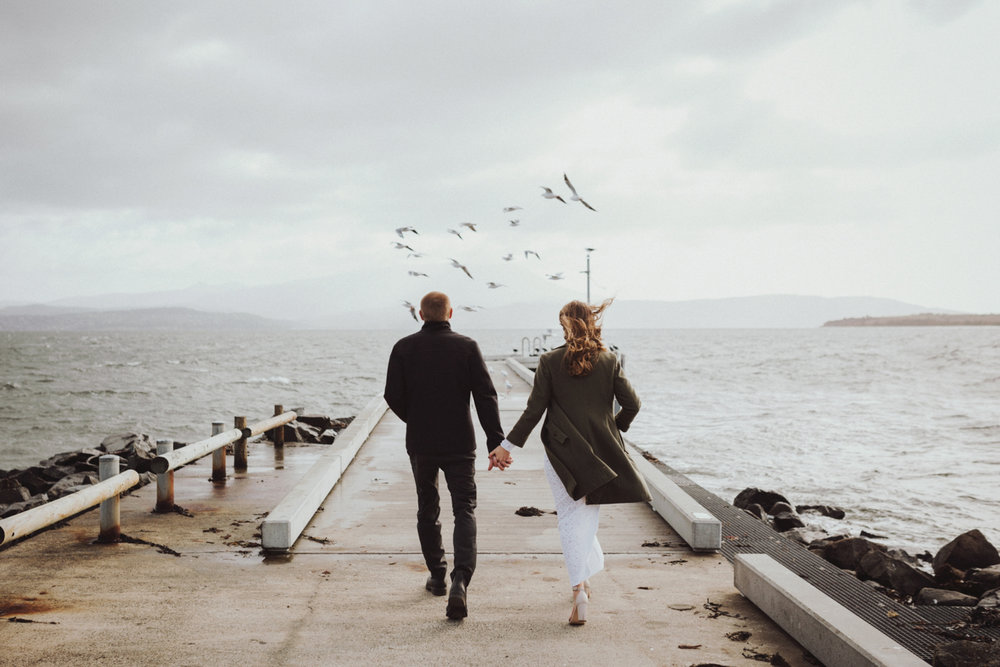 Bride and groom walk on jetty with seagulls flying ahead in tasmania.