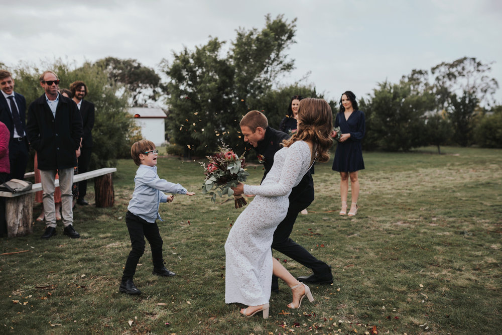 child throws confetti at bride and groom after ceremony with excited look in hobart tasmania.