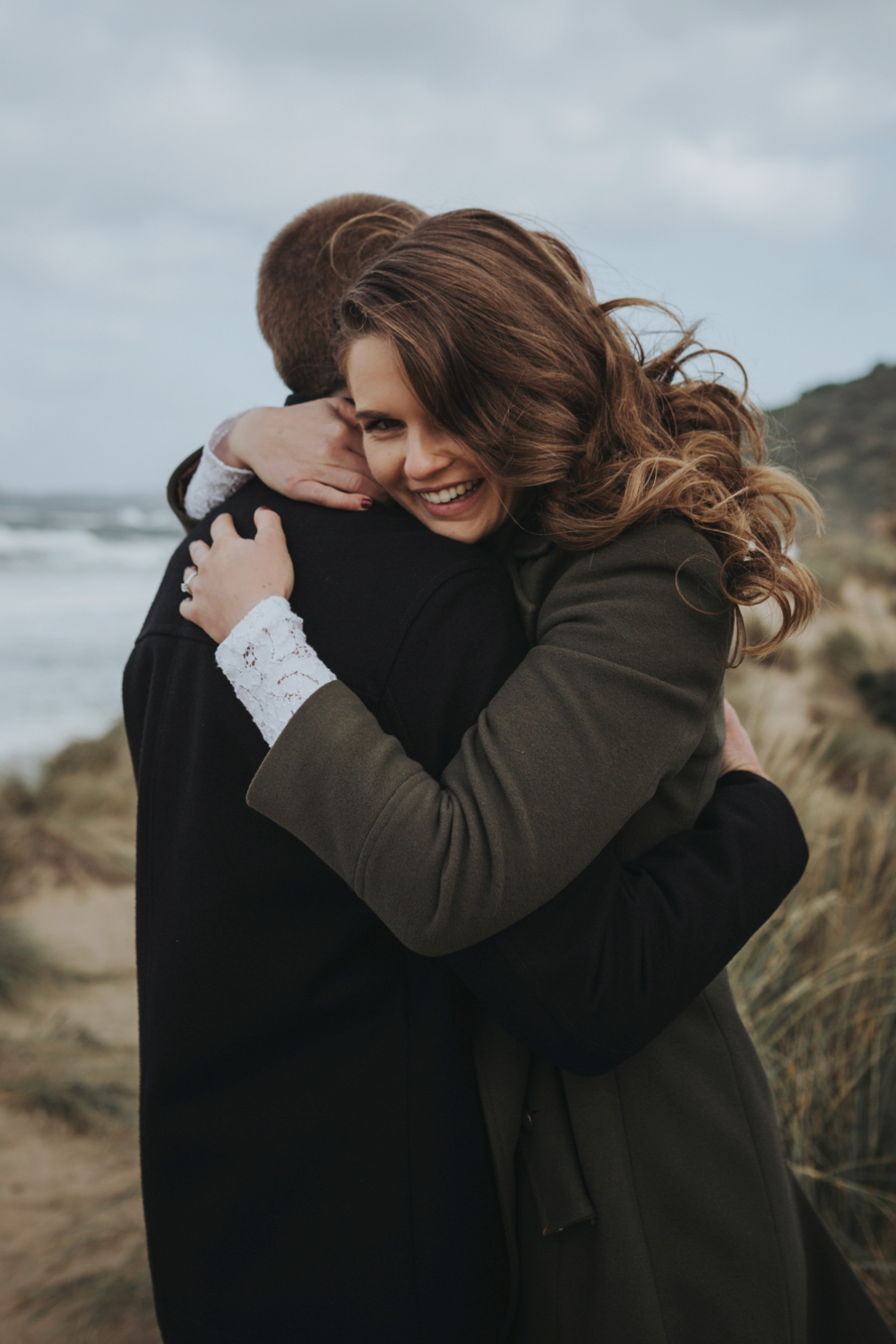 beautiful bride hugs her groom at the beach in tasmania.