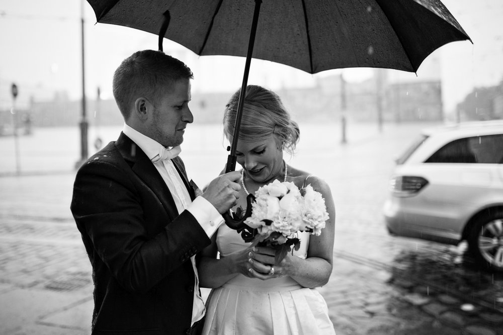 Groom holds umbrella over bride as they prepare for their wedding day in Helsinki