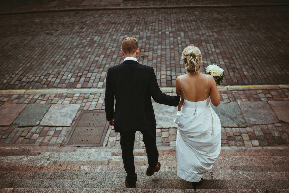 Bride and groom walk down steps into cobble stoned street on their wedding day in Finland.