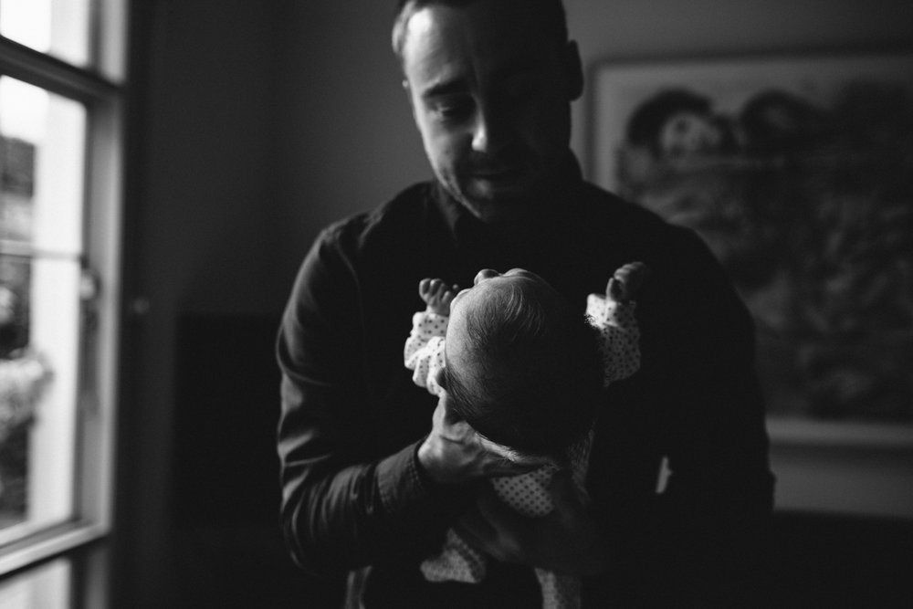 Father holds his newborn child with a look of pride.