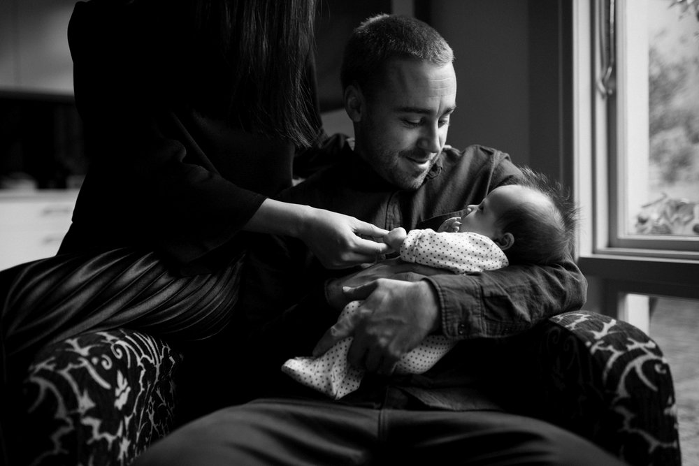 Dad stares at his newborn baby with pride during a documentary style newborn session in Hobart.