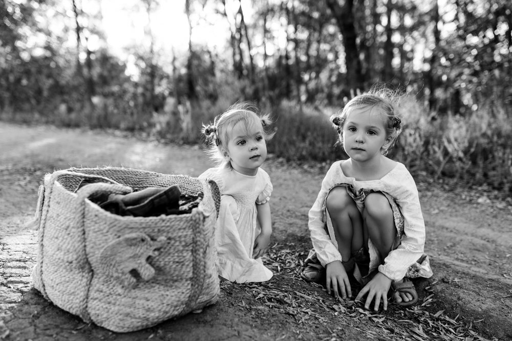 Two sisters play in the dirt during a family photography session in Brisbane.