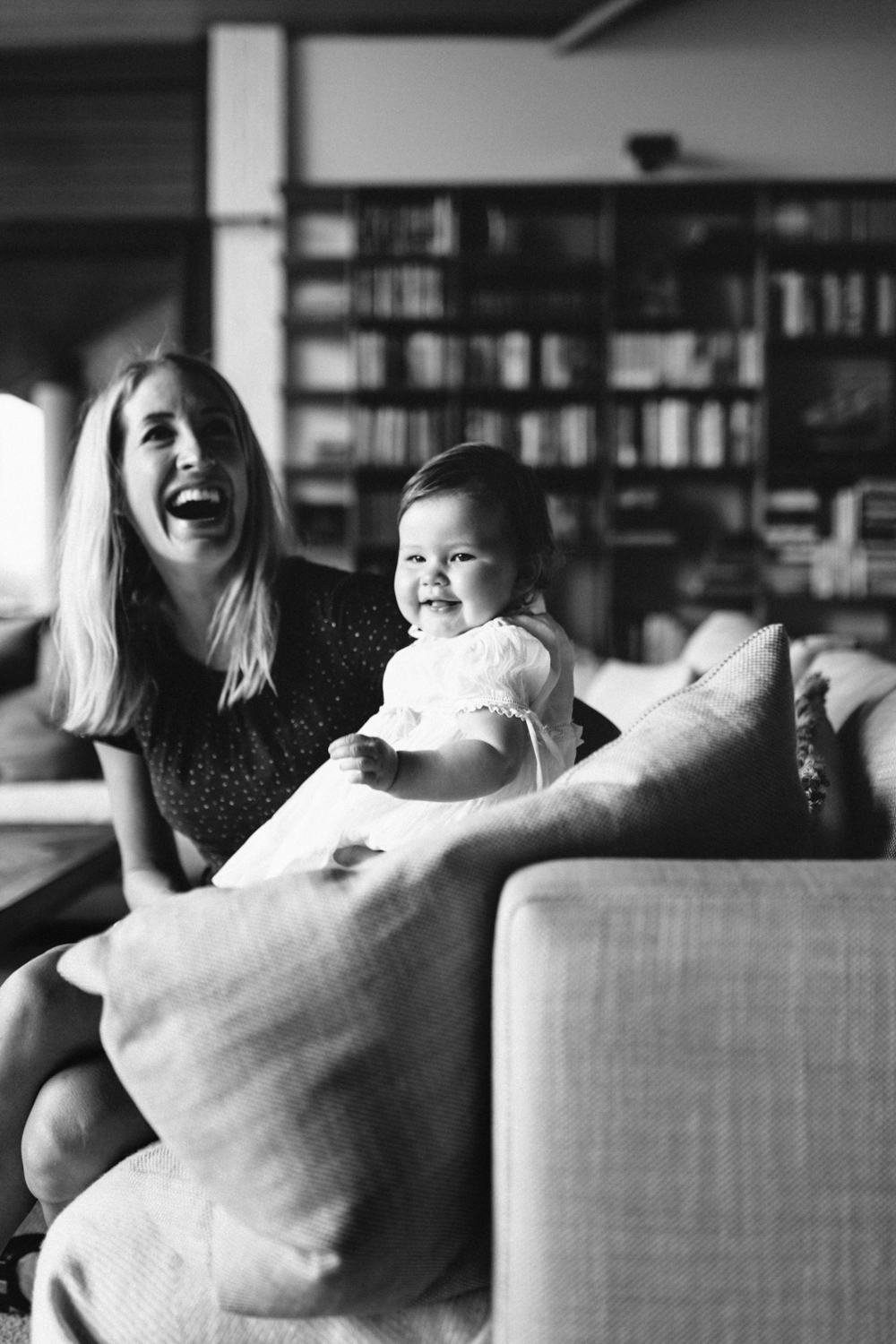 Mum and baby smile naturally during their documentary photography session at home.