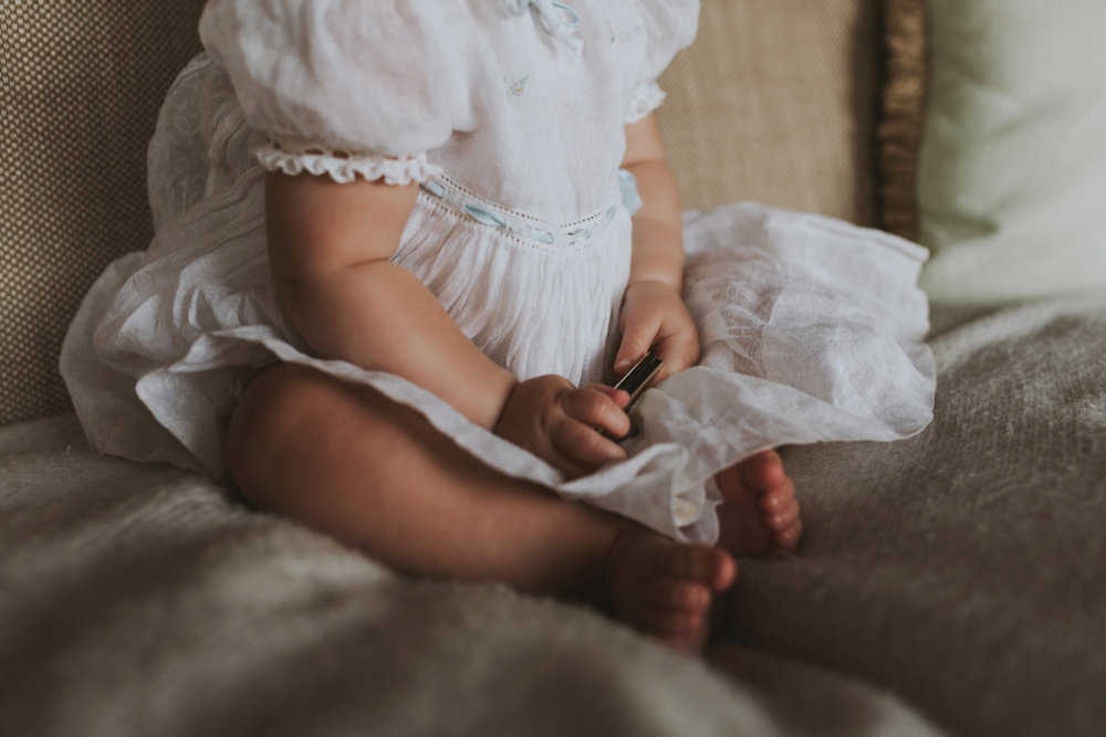 Detail shot of beautiful vintage dress on baby girl in photo session.