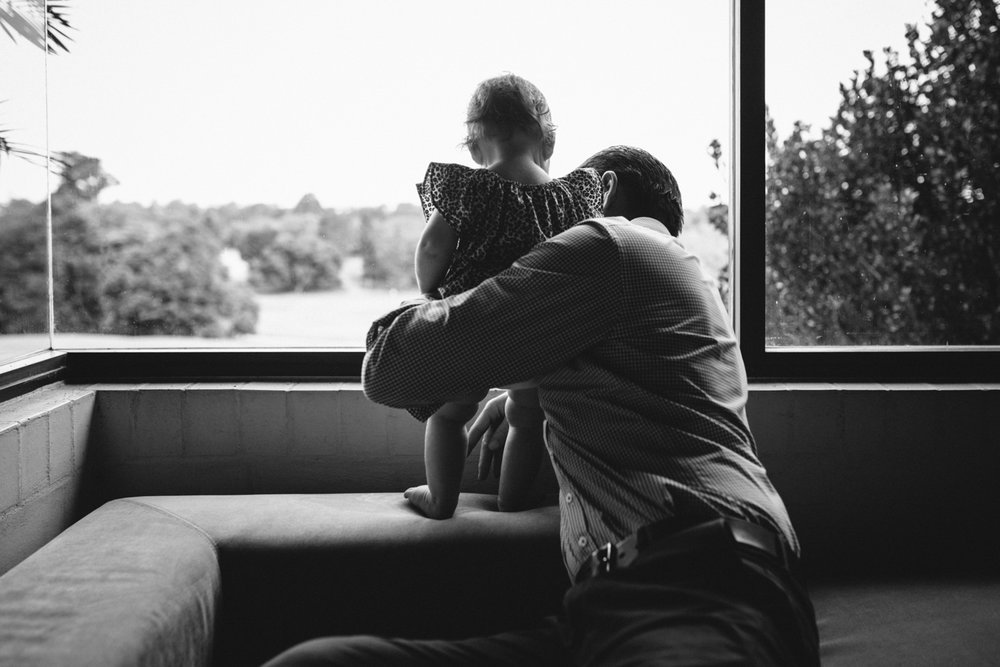 Father holds his baby daughter during a beautiful family photography session.