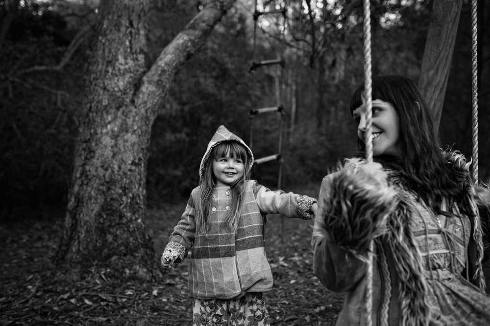Girl pushes mum on swing in a vintage pixie jacket during beautiful family photo session.